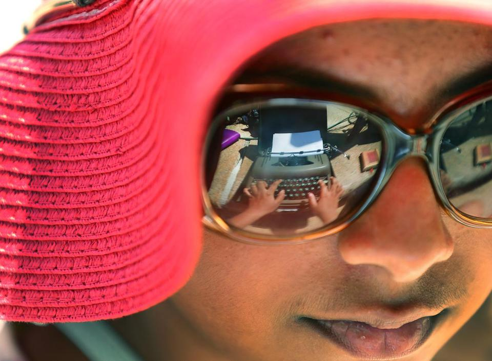 Boston-05/19/2017- Mahiti Bapuji, 12 fro Watertown has the typewriter she is working on reflected in her glasses as she types. The Boston Public Library and GrubStreet hosted a first-ever write-in on old-fashioned typewriters on the steps of the library in Copley Square. People wrote their feeling about many things including the recent rise of hatred, and immigaration concerns.John Tlumacki/ The BostonGlobe (metro)